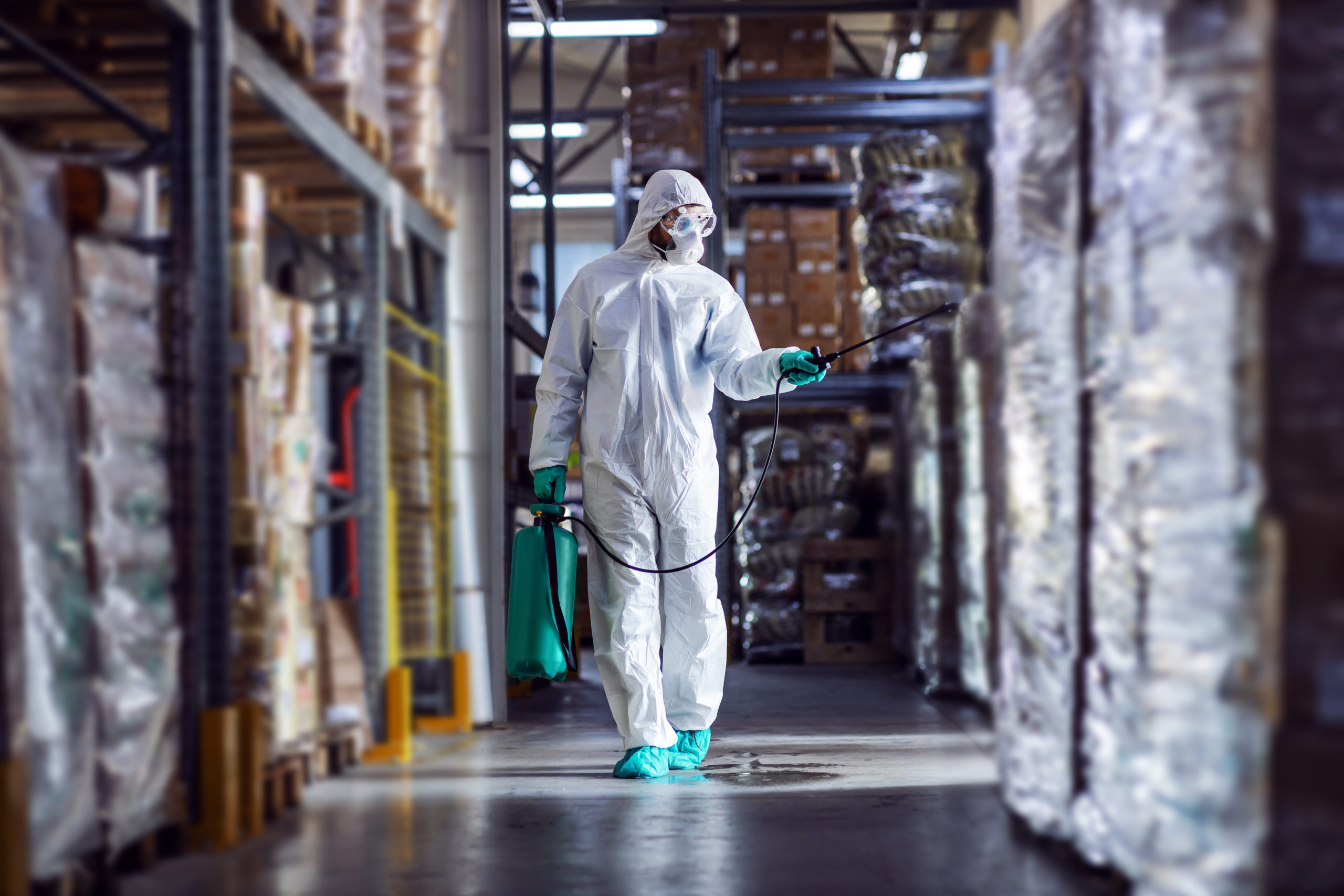 Man,In,Protective,Suit,And,Mask,Disinfecting,Warehouse,Full,Of